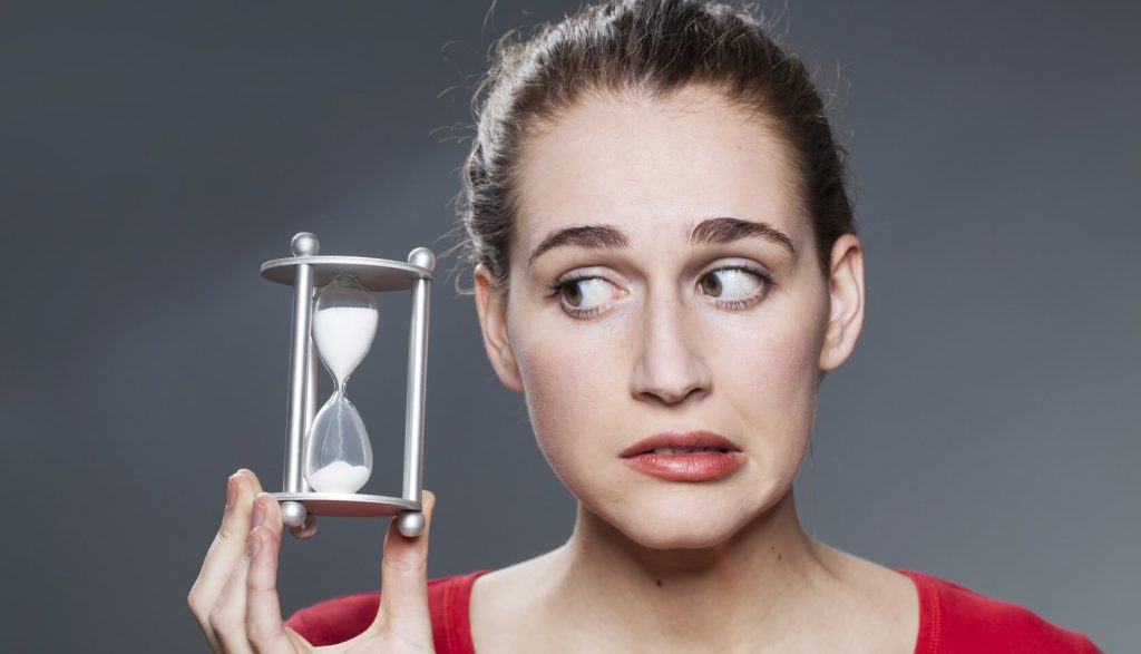 Anxious woman holding egg timer