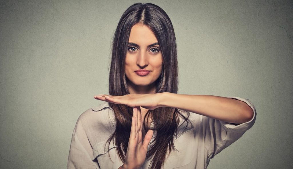 Dark haired woman making timeout hand gesture