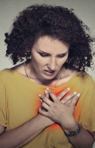 Dark haired woman suffering chest pain