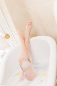 Female legs in a soapy bathtub