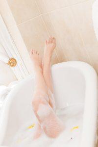 Female legs in a soapy bathtub