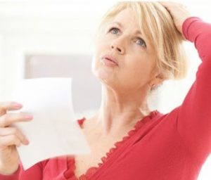 Frustrated woman examining list with hand on head