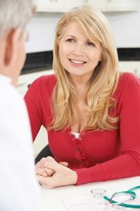 Middle aged blonde woman consults with her doctor