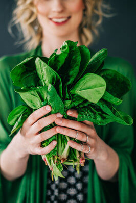 Blonde woman holding bunch of spinach leaves