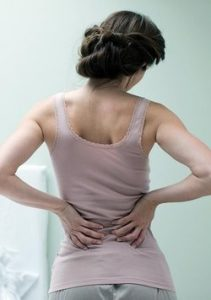 Dark haired woman clutching painful back