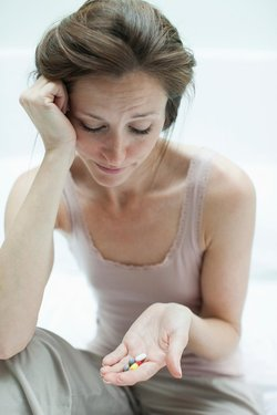 Stressed woman holding pills in hand