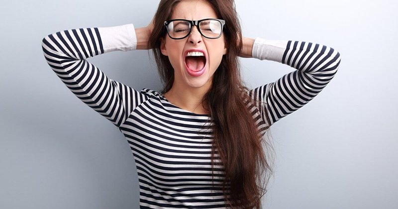 Young dark haired woman screaming with hands on head