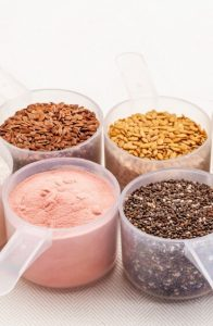 Scoops of various seeds and protein powders