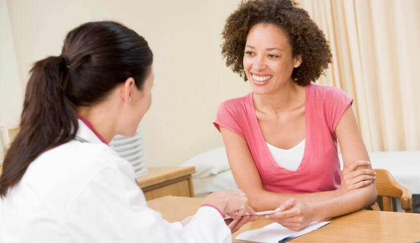 Smiling woman interacts with female doctor
