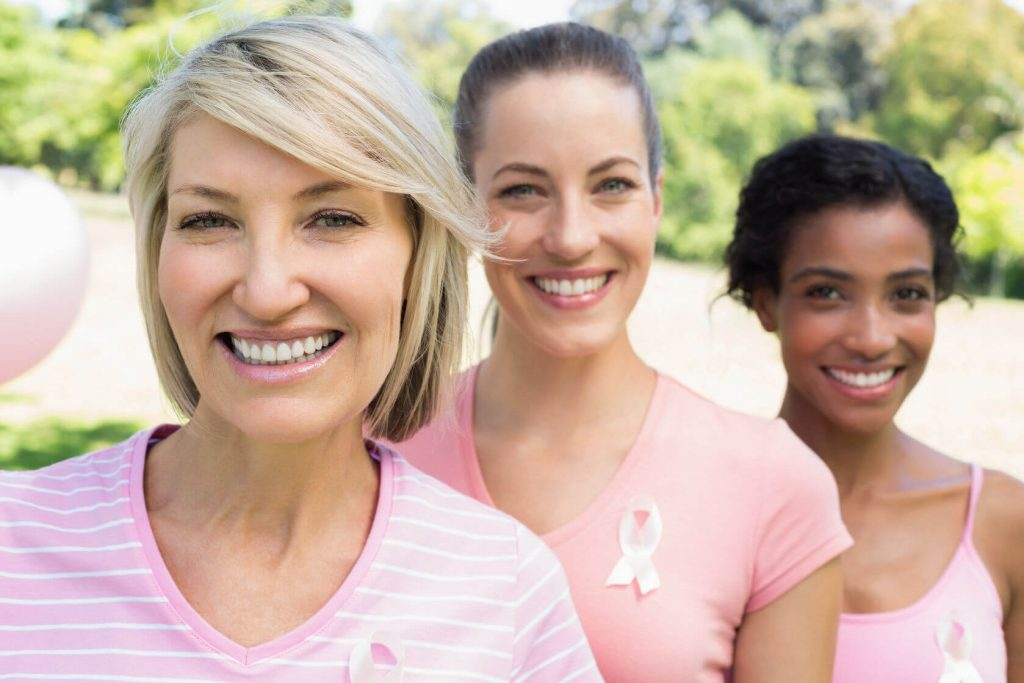 Three women stand side by side to raise breast cancer awareness