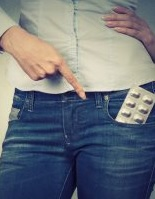 Woman pointing to pill packet in jeans