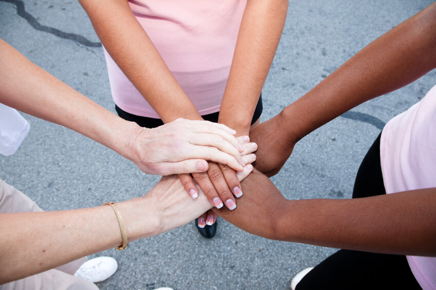 Women place hands together in solidarity