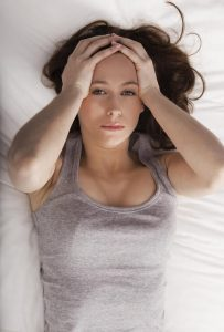 Young brunette woman clutching head on bed