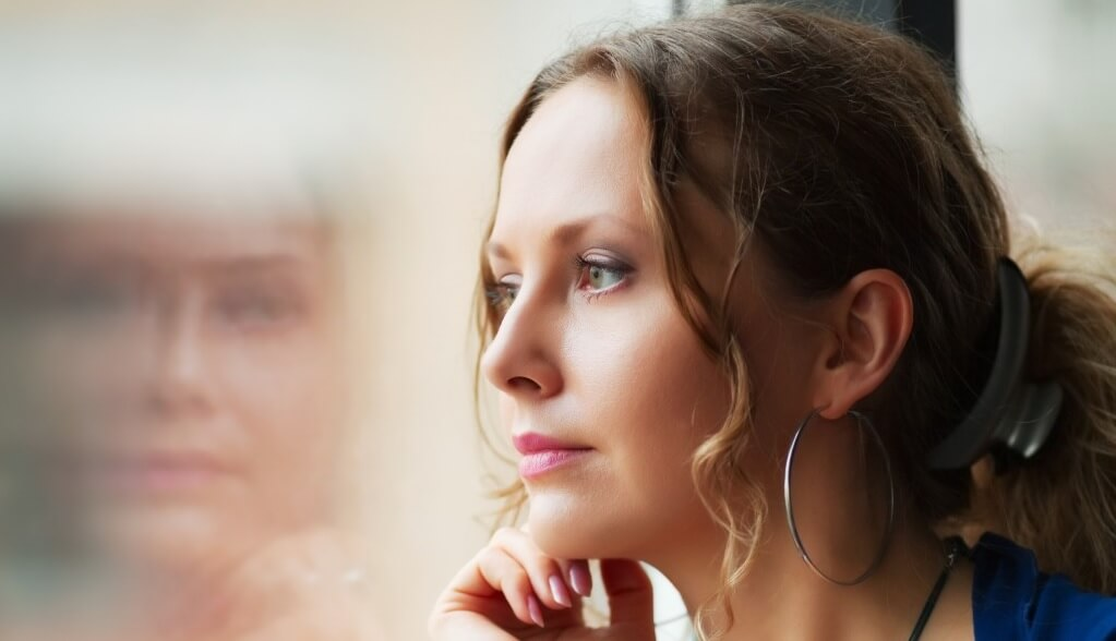 Young contemplative woman looking through window