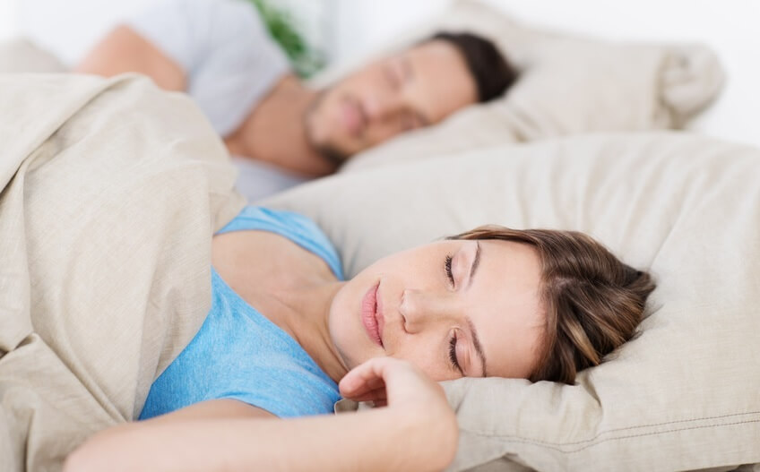 Young woman asleep on the bed beside her partner