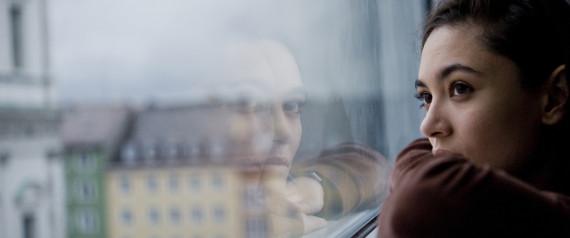 Sad contemplative woman by window