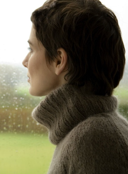 Woman looking outside on rainy day