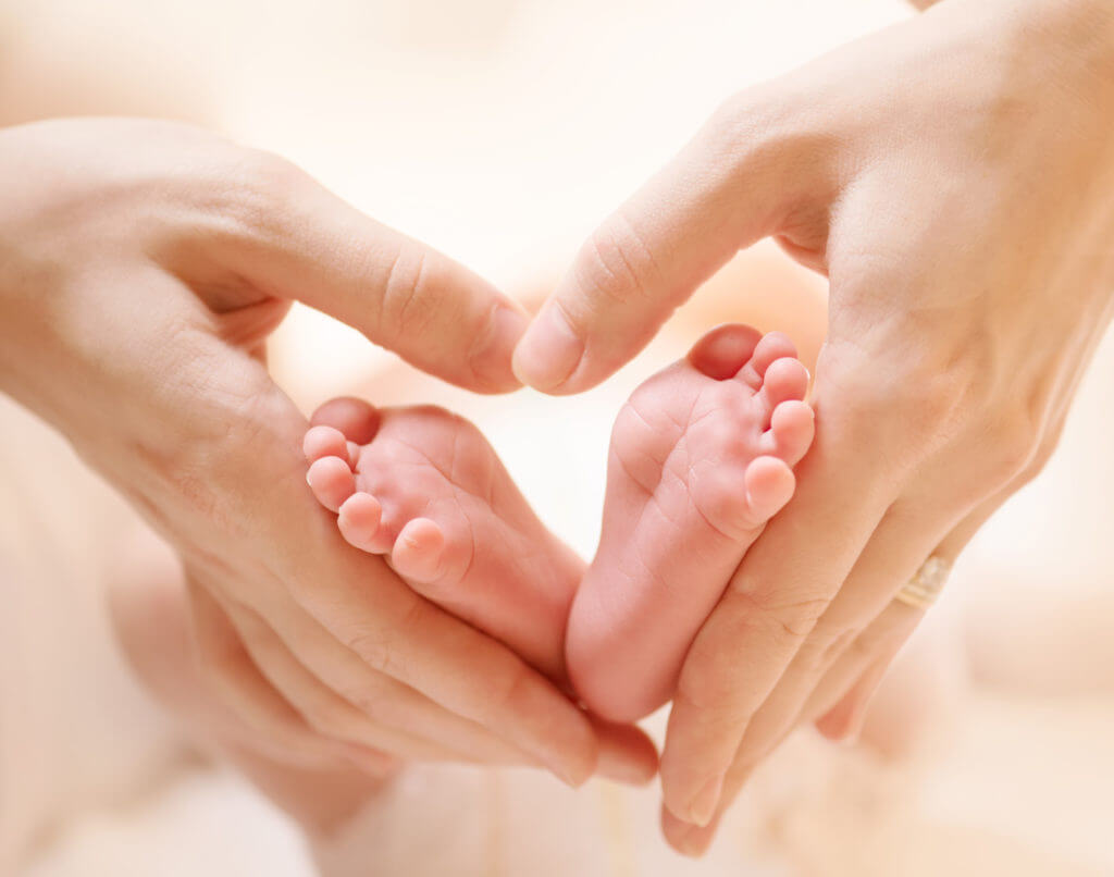 Childs feet resting in mother's hands