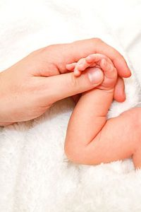 Mother cradles hand of newborn baby