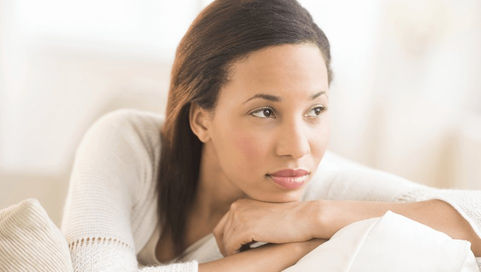 Young black woman dressed in white contemplating
