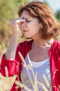 Woman suffering a menopause hot flash outdoors