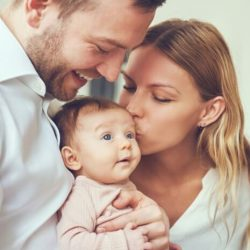 Joyous couple hold and kiss infant