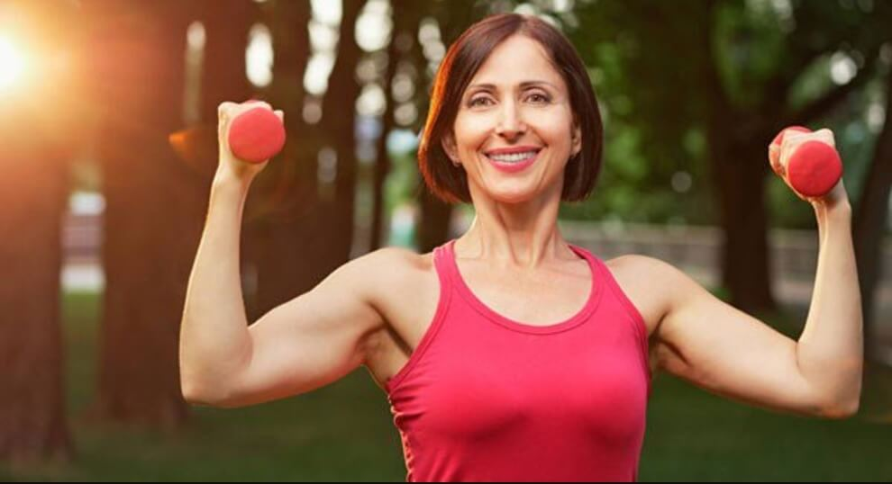 Middle aged woman lifts dumbbells at park