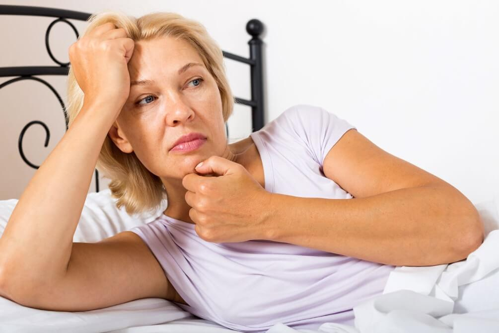 Pensive mature woman lying on bed