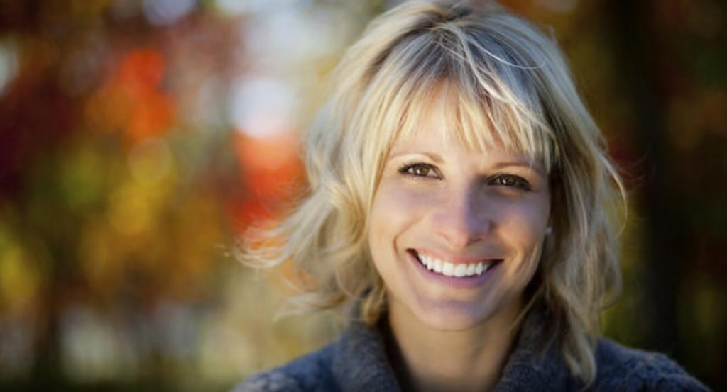 Smiling blonde middle aged woman outdoors