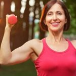 Middle aged woman lifts dumbbells outdoors