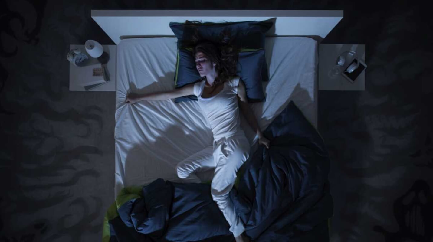 A young woman struggles to sleep